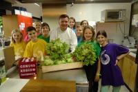 Starkoch Christof Widakovich mit den SchülerInnen bei den Kochvorbereitungen mit dem frisch geernteten Krauthäuptel